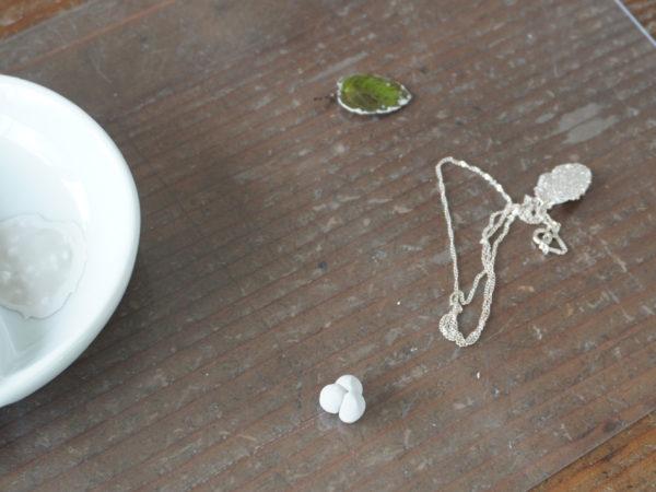 写真左側の小皿に溶いたものがペースト状の銀粘土。葉の裏側に銀粘土を塗り、ドライヤーで乾かしたところ。右側が出来上がったミントの葉をモチーフにした作品です。手前の粒は、銀粘土を手で形を作ったところ